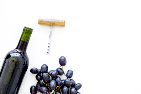 Red wine concept. Glass bottle with beverage near bunch of grapes and corkscrew on white background top view.