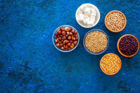 Products rich protein. Legumes, nuts, low-fat cheese. Raw beans, chickpeas, lentil, almond, hazelnut on blue background top view copy space