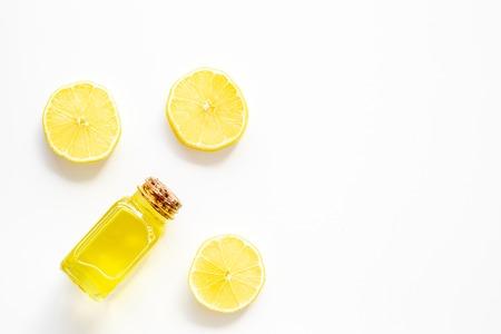 Natural cosmetics. Lemon essential oil near halfs os lemons on white background