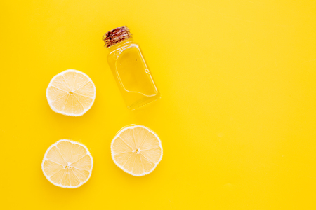 Natural cosmetics. Lemon essential oil near half os lemons on a yellow background