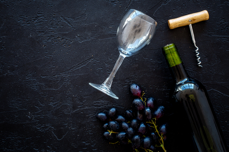 Composition with wine. Red wine bottle, bunch of grapes, corkscrew, wine glass on black background
