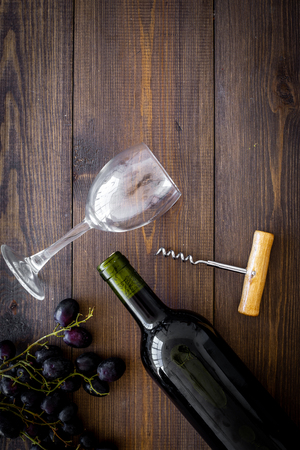 Composition with wine. Red wine bottle, bunch of grapes, corkscrew, wine glass on dark wooden background