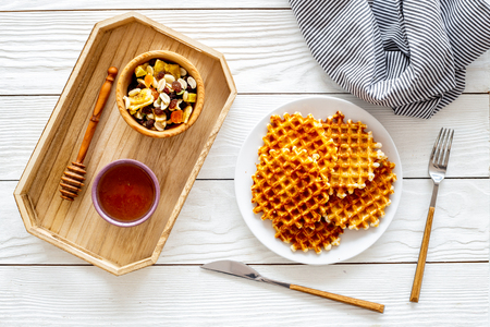 Round belgian waffles for breakfast. Breakfast in bed. Waffles on plate. Honey and dried fruits in tray, knife and fork, tablecloth on white wooden background top view.