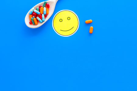 Reception of medicines concept. Recovery. Pills in spoon near smile face emoji on blue background top view