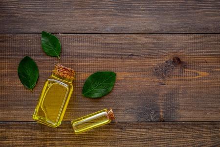 Tea tree essential oil near tea tree leaves on dark wooden background top view copy space