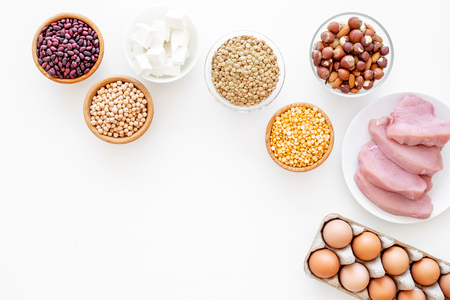 Healthy food. Products rich protein and fiber. Legumes, nuts, low-fat cheese, meet, eggs. Raw beans, chickpeas, lentil, almond, hazelnut on white background top view copy space