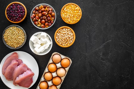 Food for sportsmen. Legumes, nuts, low-fat cheese, meet, eggs on black background top view copy space Stock Photo