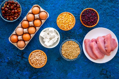 Food for sportsmen. Legumes, nuts, low-fat cheese, meet, eggs on blue table top view Stock Photo