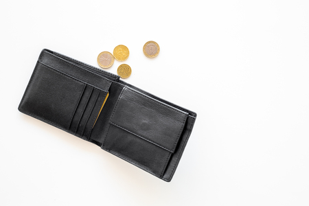 Unemployment concept. Lack of money. Coins fall out of wallet on white background top view copy space