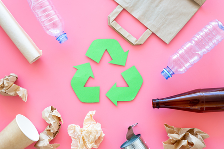 Recycling. Green recycle eco symbol. Recycled arrows sign near materials for recycle and reuse on pink background top view. Foto de archivo - 107003385