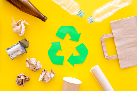 Recycling. Green recycle eco symbol. Recycled arrows sign near materials for recycle and reuse on yellow background top view.