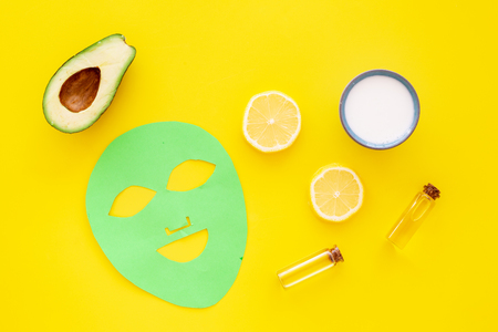Skin care. Facial mask, cream and lotion near avocado and lemon on yellow background top view