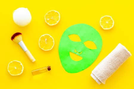 Skin care. Facial mask, cream and lotion near lemon slices on yellow background top view Stock Photo