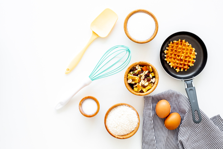 Preparing belgian waffles. Waffle on pan near whisk for whipping and ingrdients. Eggs, flour, sugar, dried fruits on white background top view.
