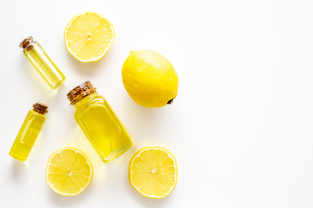 Natural cosmetics. Lemon essential oil near halfs os lemons on white background top view. 스톡 콘텐츠 - 107069363
