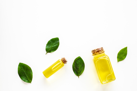 Tea tree essential oil near tea tree leaves on white background top view. Stock Photo - 107069365