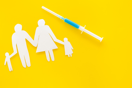 Vaccination for healthy family, vacctination of children. Flu. Syringe near family cutout on yellow background top view.