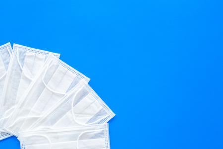 Flu prevention. Medical face masks on blue background top view.
