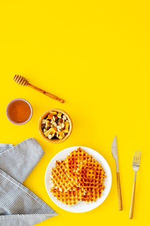 Hot round waffles ready to eat. Belgian recipe. Waffles on plate near honey and dried fruits on yellow background top view. Stock Photo