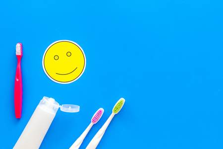 Teeth care, dental care. Toothbrushes and tooth paste near smile face emoji on blue background top view.