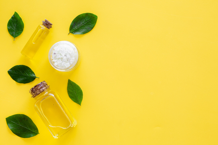 Natural hipoallergenic cosmetics with tea tree essential oil. Oil, lotion, leaves on yellow background top view copy space Stock Photo