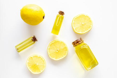 Natural cosmetics. Lemon essential oil near halfs os lemons on white background top view closeup Stock Photo
