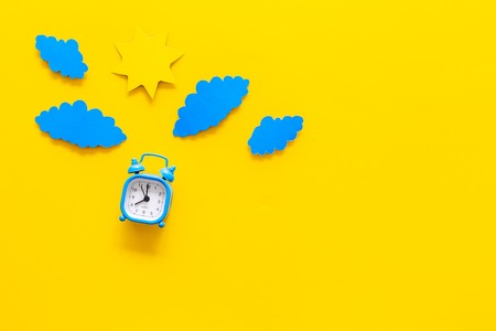 Time of day. Morning. Awakening and sunrise. Sun and clouds cutout near alarm clock on yellow background top view.