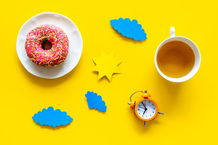 Time for breakfast concept. Tea, donut near alarm clock, sun and clouds cutout on yellow background top view.