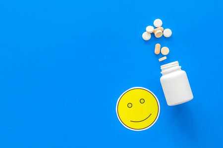 Reception of medicines concept. Recovery. Pills falling out of jar near smile face emoji on blue background top view.