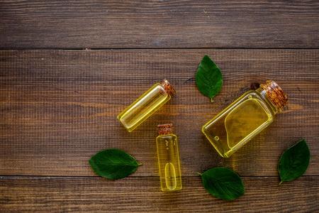 Tea tree essential oil near tea tree leaves on dark wooden background top view.