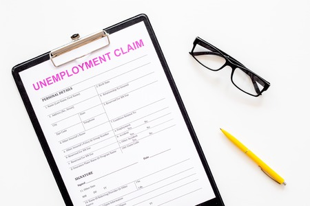 Unemployment claim form on white background top view.