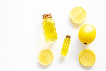 Natural cosmetics. Lemon essential oil near halfs os lemons on white background top view. 스톡 콘텐츠 - 107200784