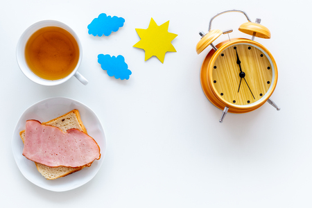 Parts of day. Morning. Time for breakfast. Tea, sandwich near alarm clock, sun and clouds cutout on white background top view. Reklamní fotografie