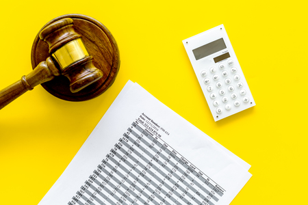 Bankruptcy concept. Judge gavel, documents, calculator on yellow background top view
