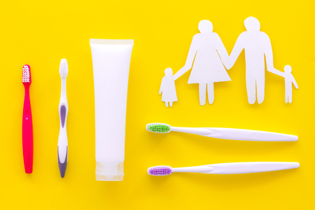 Teeth care, dental care. Toothbrushes and tooth paste near family silhouette on yellow background top view. Stock Photo