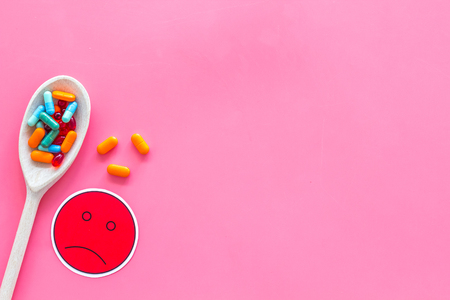Illness. Drug intake. Pills in spoon near sad face emoji on pink background top view space for text