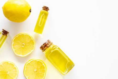 Natural cosmetics. Lemon essential oil near halfs os lemons on white background top view.