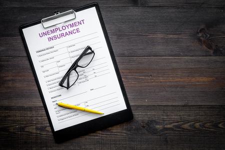 Unemployment insurance form on dark wooden background top view.