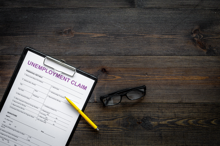 Unemployment claim form on dark wooden background top view.