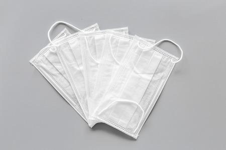 Flu prevention. Medical face masks on grey background top view.