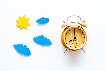 Time of day. Morning. Awakening and sunrise. Sun and clouds cutout near alarm clock on white background top view.