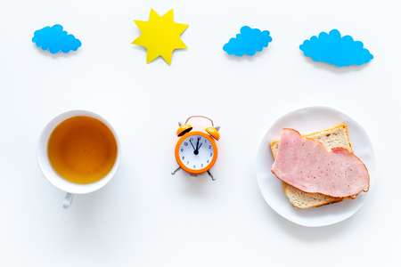 Parts of day. Morning. Time for breakfast. Tea, sandwich near alarm clock, sun and clouds cutout on white background top view. Stock Photo