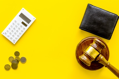 Financial failure, bankruptcy concept. Judge gavel, wallet, coins calculator on yellow background