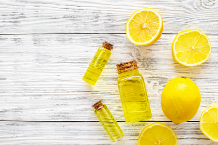 Organic cosmetics with natural ingredients. Lemon essential oil near halfs os lemons on white wooden background top view.