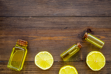 Organic cosmetics with natural ingredients. Lemon essential oil near halfs os lemons on dark wooden background top view. Stock Photo