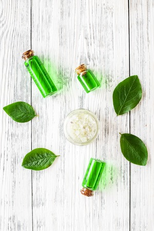 Natural hipoallergenic cosmetics with tea tree essential oil. Oil, lotion, leaves on white wooden background top view. Stock fotó - 107350530