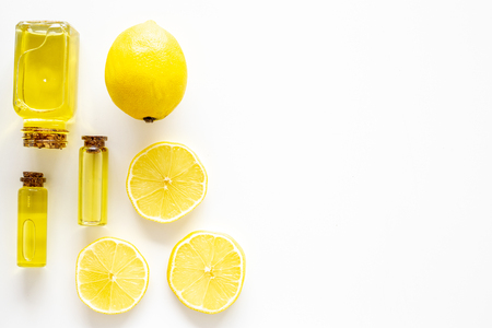 Natural cosmetics. Lemon essential oil near halfs os lemons on white background top view closeup space for text 스톡 콘텐츠