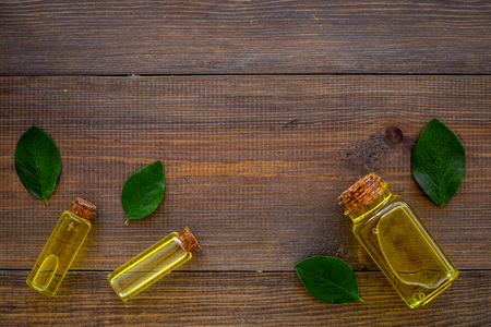 Tea tree essential oil near tea tree leaves on dark wooden background top view copy space