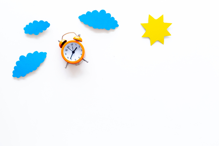 Time of day. Morning. Awakening and sunrise. Sun and clouds cutout near alarm clock on white background top view space for text 写真素材