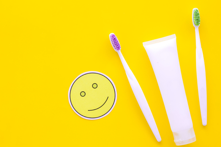 Teeth care, dental care. Toothbrushes and tooth paste near smile face emoji on yellow background top view copy space Stock Photo